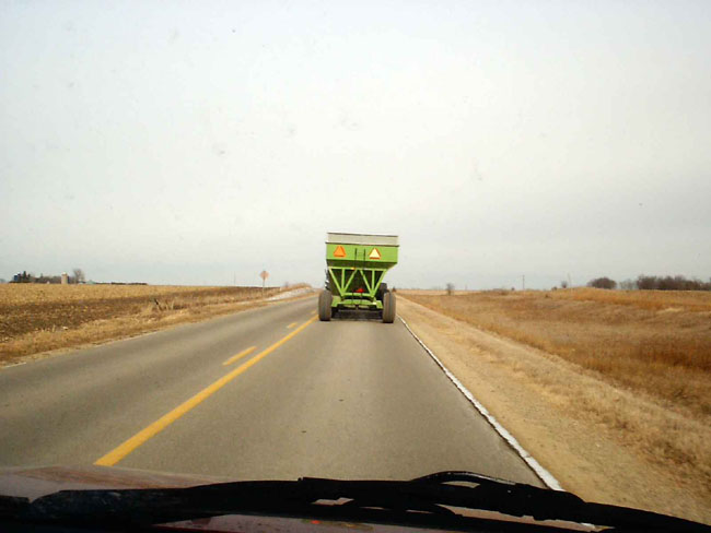 """Here we are following a tractor pulling a grain wagon down the highway."""